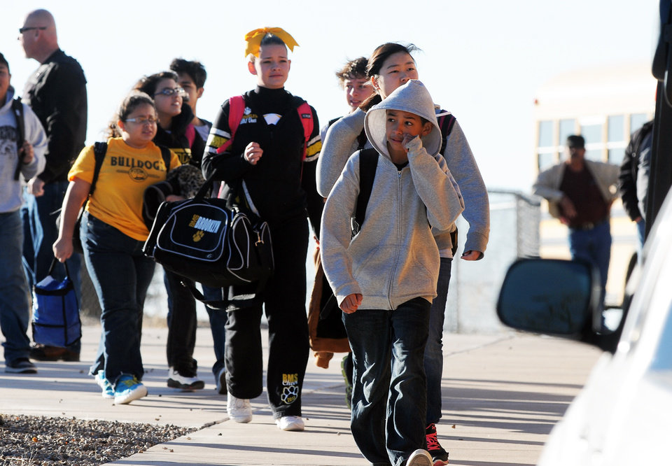 Photo - Students are escorted from Berrendo Middle School after a shooting, Tuesday, Jan. 14, 2014, in Roswell, N.M. A shooter opened fire at the middle school, injuring at least two students before being taken into custody. Roswell police said the school was placed on lockdown. (AP Photo/Roswell Daily Record, Mark Wilson)