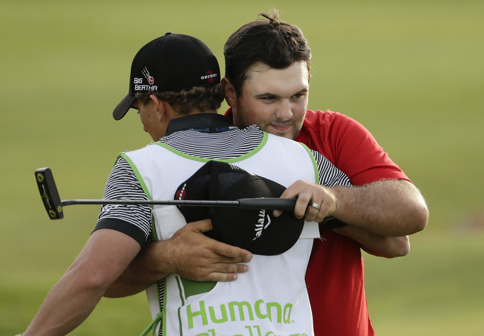 Photo - Patrick Reed, right, hugs his caddie Kessler Karain after winning the Humana Challenge golf tournament on the Palmer Private course at PGA West Sunday, Jan. 19, 2014 in La Quinta, Calif. (AP Photo/Chris Carlson)