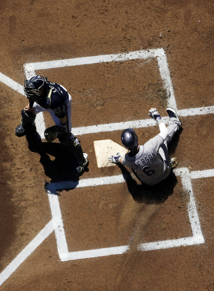 Photo - Colorado Rockies' Corey Dickerson slides home safely past Milwaukee Brewers catcher Jonathan Lucroy during the first inning of a baseball game Sunday, June 29, 2014, in Milwaukee. Dickerson scored from second on a hit by Wilin Rosario. (AP Photo/Morry Gash)