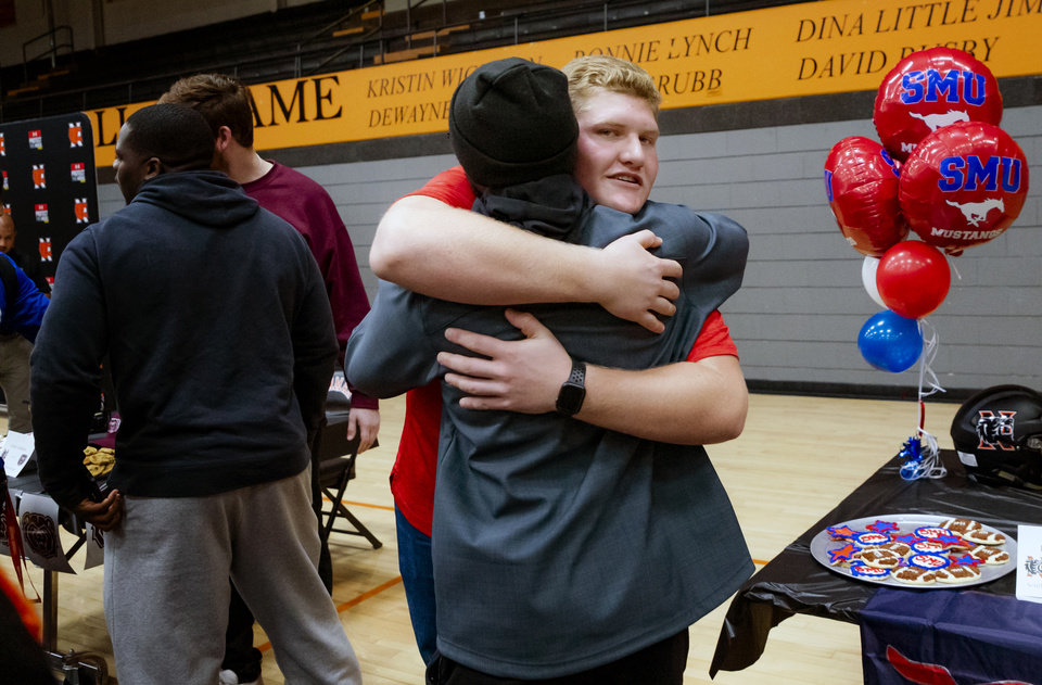 Photo - Southern Methodist University signee Ben Sparks, right, celebrates signing his letter of intent with classmates during a national signing day ceremony for football at Norman High School in Norman Okla. on Wednesday, Dec. 18, 2019.   [Chris Landsberger/The Oklahoman]
