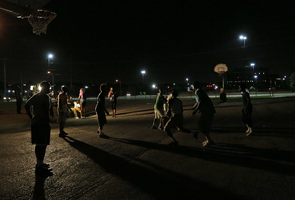 Photo - Youth play basketball on a court lit only by one shop light during midnight basketball at Christ Temple Community Church in Oklahoma City, Friday, July 25, 2014. Photo by Sarah Phipps, The Oklahoman