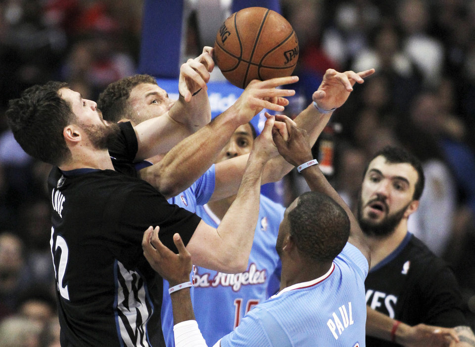 Photo - Minnesota Timberwolves forward Kevin Love, left, battles Los Angeles Clippers forward Blake Griffin, second from left, center Ryan Hollins, center, and guard Chris Paul, second from right as Timberwolves center Nikola Pekovic, right, of Montenegro, stands near in the first half of an NBA basketball game in Los Angeles on Sunday, Dec. 22, 2013. (AP Photo/Alex Gallardo)
