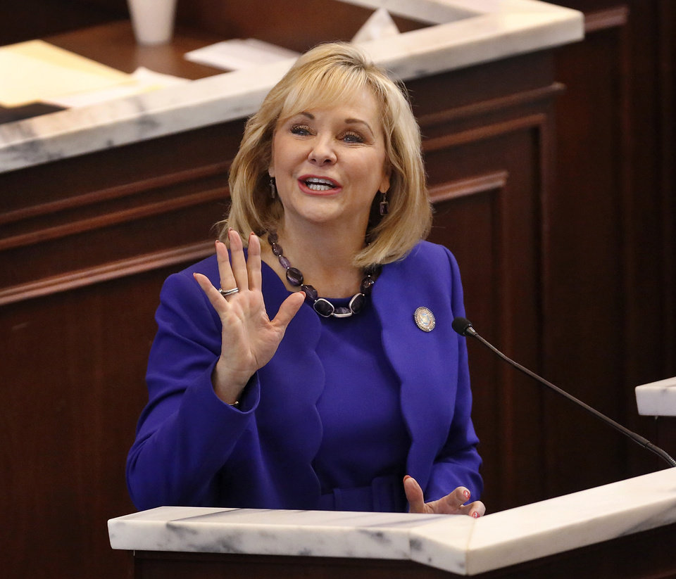 Photo - Gov. Mary Fallin waves and sends a kiss to her family seated in the gallery at the beginning of her speech. Fallin outlined her goals for the upcoming legislative session during her state of the state speech to a joint session of the legislature in the House chamber at the state Capitol on Monday, Feb. 3, 2014.   Photo by Jim Beckel, The Oklahoman