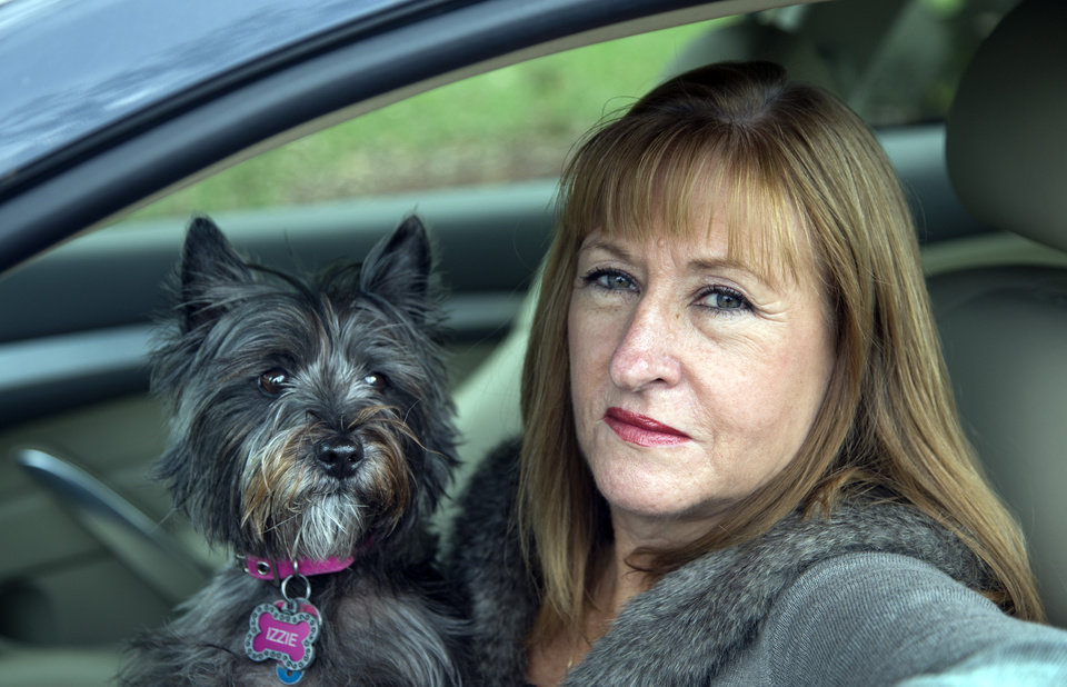 Photo -   In this photo taken Nov. 2, 2012, Diane Spitaliere and her pet dog Izzie sit in her car outside her house in Alexandria. Baby boomers, that giant population bubble born between 1946 and 1964, started driving at a young age and became more mobile than any generation before or since. Spitaliere, a 58-year-old who recently retired after working 38 years at the Federal Aviation Administration, said the idea of moving to a retirement or assisted living community