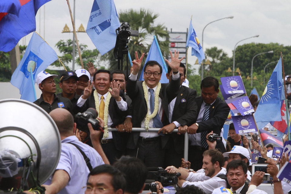 Photo - Sam Rainsy, center right, president of Cambodia National Rescue Party (CNRP) greets his supporters together with his party's Vice President Kem Sokha, center left, on his arrival at Phnom Penh International Airport in Phnom Penh, Cambodia, Friday, July 19, 2013. Thousands of cheering supporters greeted Cambodian opposition leader Sam Rainsy as he returned from self-imposed exile Friday to spearhead his party's election campaign against well-entrenched Prime Minister Hun Sen. (AP Photo/Heng Sinith)