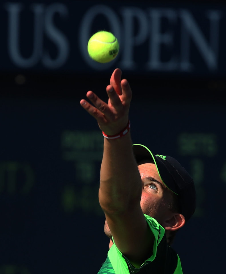 Photo - Dominic Thiem, of Austria, serves against Ernests Gulbis, of Latvia, during the second round  of the 2014 U.S. Open tennis tournament, Friday, Aug. 29, 2014, in New York. (AP Photo/John Minchillo)