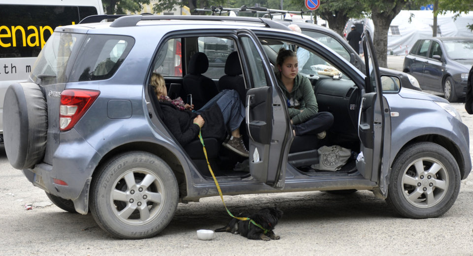 Photo -   People take shelter in a car in Finale Emilia, some 60 kilometers east of Bologna in northern Italy, after the region was hit by an earth quake early Sunday, May 20, 2012. One of the strongest earthquakes to shake northern Italy rattled the region around Bologna early Sunday, a magnitude-6.0 temblor that killed at least four people, toppled buildings and sent residents running into the streets, emergency services and news reports said. (AP Photo/Marco Vasini)