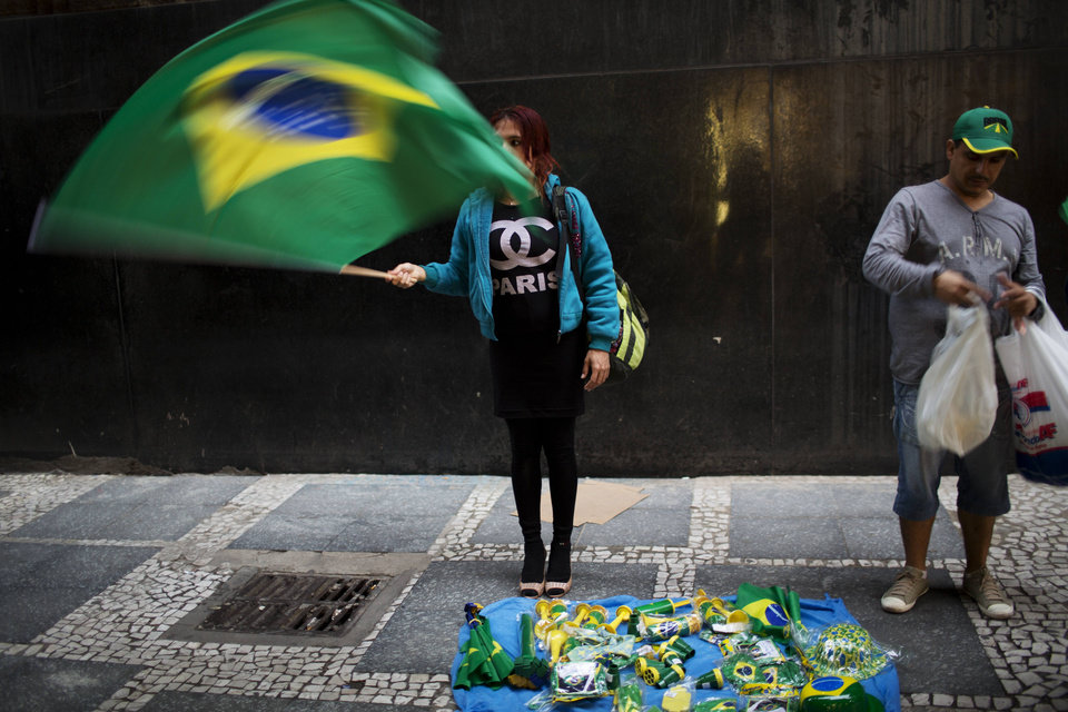 Photo - A couple sell Brazilian flags in downtown Sao Paulo, Brazil, Tuesday, June 10, 2014. The 2014 World Cup is set to begin Thursday, with Brazil and Croatia competing in the opening match in Sao Paulo. (AP Photo/Rodrigo Abd)