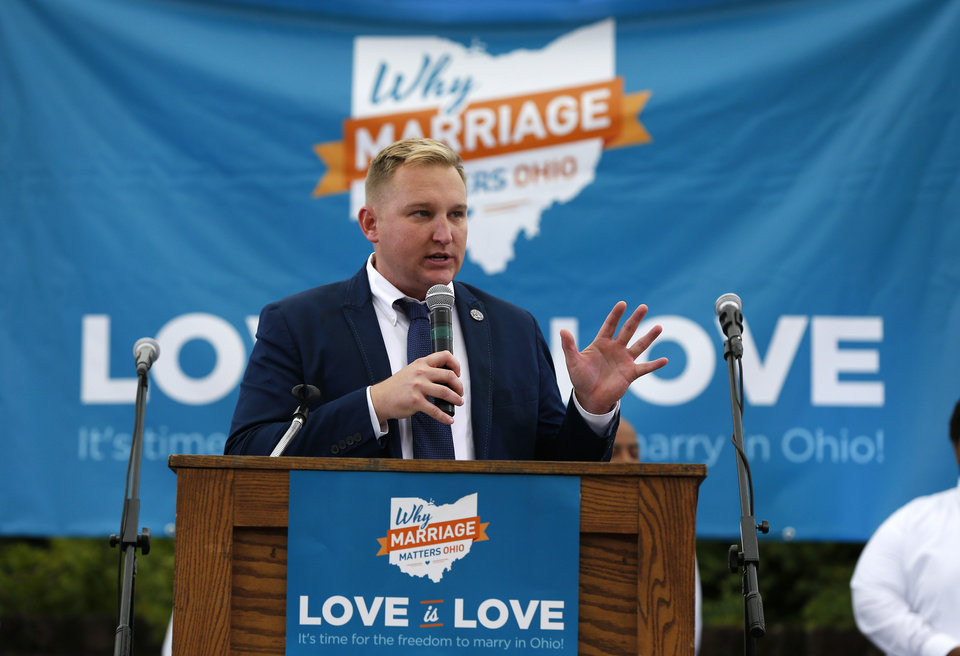 Photo - Chris Seelbach, the first openly-gay politician elected and currently sitting on the Cincinnati City Council, speaks in front of hundreds along with the group Why Marriage Matters Ohio at a rally for gay marriage in Lytle Park, Tuesday, Aug. 5, 2014 in Cincinnati. Federal appeals courts soon will hear arguments in gay marriage fights from nine states, part of a slew of cases putting pressure on the U.S. Supreme Court to issue a final verdict. (AP Photo/The Cincinnati Enquirer, Jeff Swinger)
