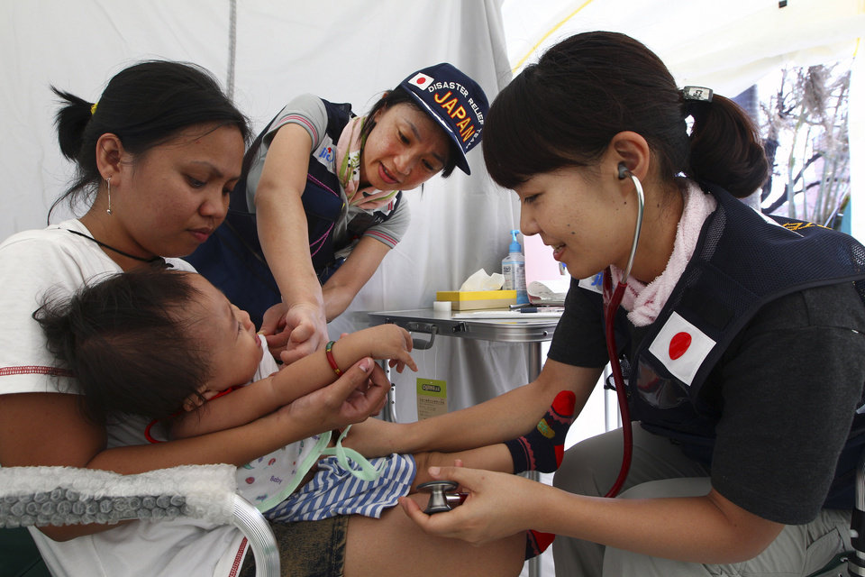 Photo - Japanese doctors examine a baby in a field hospital set up for people who are affected by Typhoon Haiyan in Tacloban, Philippines, Saturday, Nov. 16, 2013. Typhoon Haiyan, one of the most powerful storms on record, hit the country's eastern seaboard Nov. 8, leaving a wide swath of destruction. (AP Photo/Dita Alangkara)