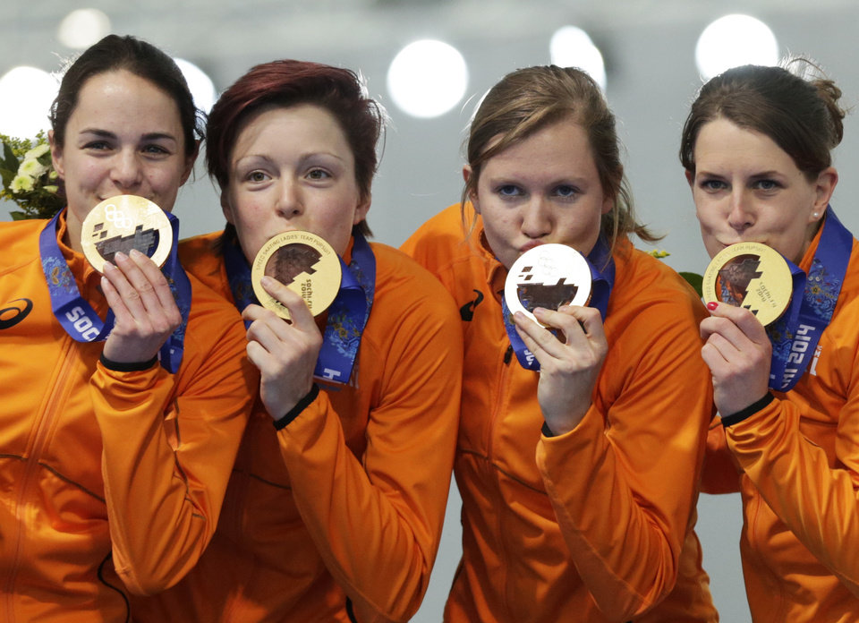 Photo - Gold medallists from team Netherlands, left to right, Marrit Leenstra, Jorien ter Mors, Lotte van Beek, and Ireen Wust kiss their medals during the medal ceremony for the women's team pursuit at the Adler Arena Skating Center at the 2014 Winter Olympics, Saturday, Feb. 22, 2014, in Sochi, Russia. (AP Photo/Matt Dunham)