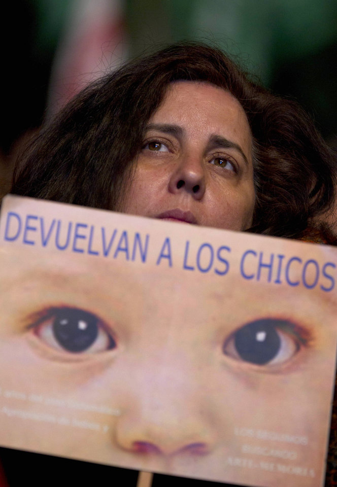 Photo -   A woman holds a sign that reads in Spanish