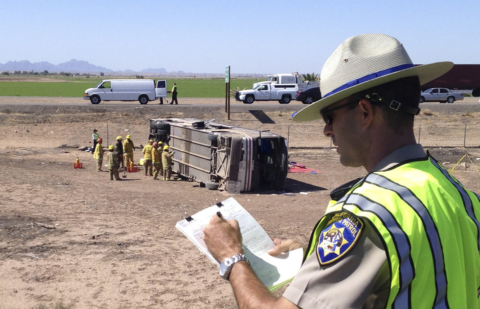 Photo - California Highway Patrol Officer Kevin Long goes over paperwork at the site of a bus crash Wednesday May 21, 2014 in Blythe, Calif. Authorities said a tractor-trailer spilled a load of steel pipes onto a highway, triggering a bus crash Wednesday that killed four people and seriously injured at least seven others on the main road linking Southern California and Arizona. (AP Photo/Brian Skoloff)