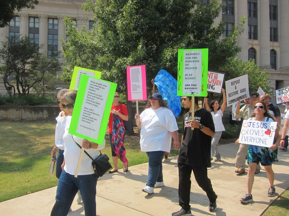 Photo -  group walks around the State Capitol as part of a prayer gathering Saturday to show support for the Ten Commandments monument on capitol grounds. [Photo by Carla Hinton, The Oklahoman]