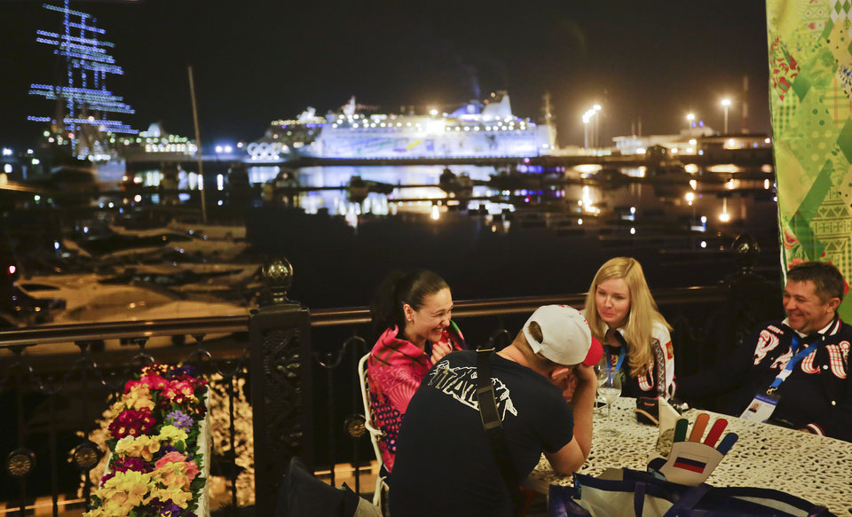 Photo - Patrons sit out at a restaurant along the seaport on the Black Sea, Saturday, Feb. 15, 2014, in central Sochi, Russia, home of the 2014 Winter Olympics. (AP Photo/David Goldman)