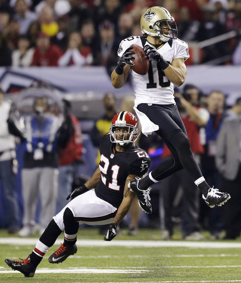 New Orleans Saints wide receiver Lance Moore (16) makes a catch in front of Atlanta Falcons defensive back Chris Owens (21) during the first half of an NFL football game, Thursday, Nov. 29, 2012, in Atlanta. (AP Photo/David Goldman)