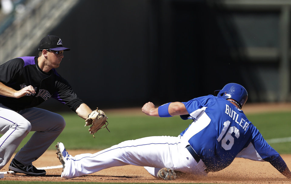 Photo - Colorado Rockies second baseman DJ LeMahieu, left, waits to tag out Kansas City Royals' Billy Butler during the fourth inning of a  spring training baseball game Tuesday, March 19, 2013, in Surprise, Ariz. (AP Photo/Gregory Bull)