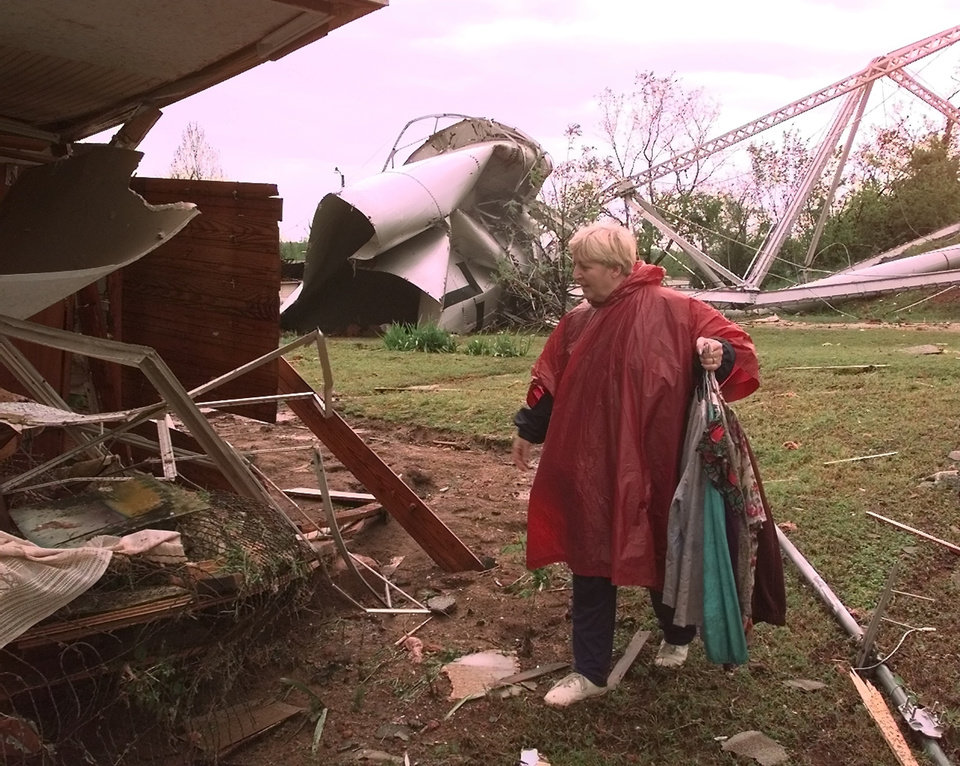 MAY 3, 1999 TORNADO: Tornado damage. Alice Magee carries clothes salvaged from her mother's home in Mulhall.  Water from the collapsed water tower pushed the house twelve feet off of its foundation with Kathryn Harris, 76, inside.