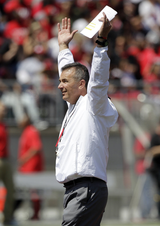 Photo - Ohio State head coach Urban Meyer raises his arms during a spring NCAA college football game Saturday, April 12, 2014, in Columbus, Ohio. (AP Photo/Jay LaPrete)