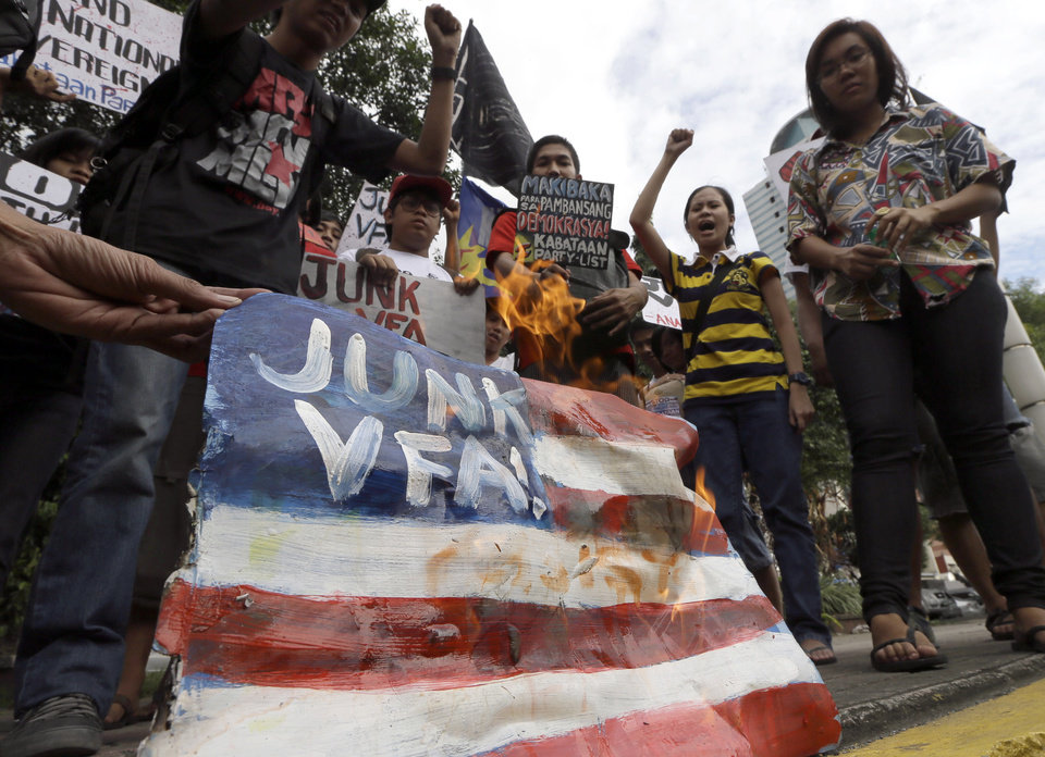 Protesters burn a mock American flag during a rally at the U.S. Embassy in Manila to protest the recent incident in the Philippines wherein a U.S. Navy minesweeper, USS Guardian, ran aground off Tubbataha Reef, a World Heritage Site in the Sulu Sea, 640 kilometers (400 miles) southwest of Manila, Philippines Saturday Jan. 19, 2013. The protesters are demanding the abrogation of the Visiting Forces Agreement which allows U.S. troops\' presence in the country. (AP Photo/Bullit Marquez)