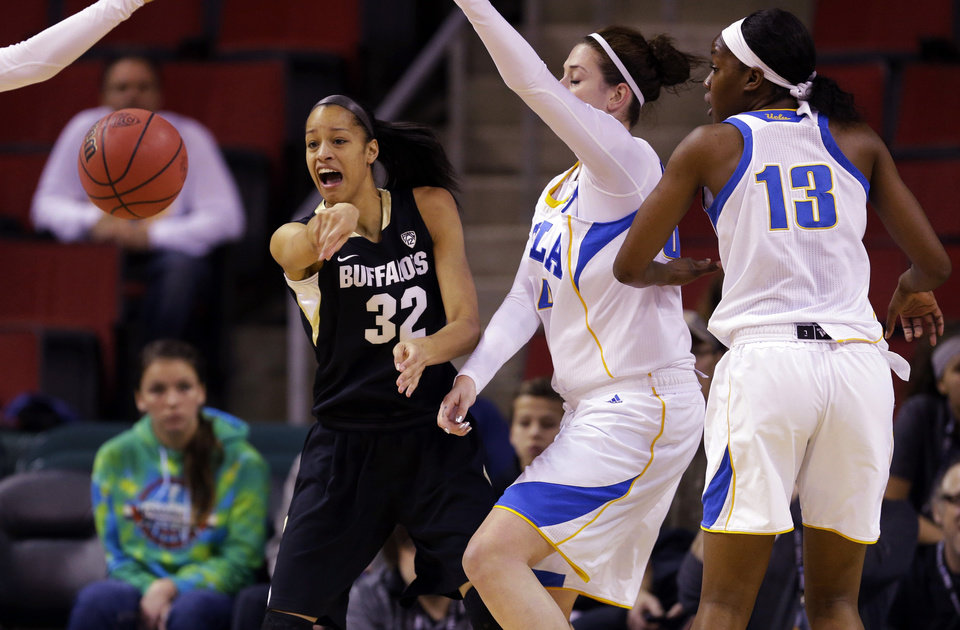 Photo - Colorado forward Arielle Roberson (32) passes around the defense of UCLA's Luiana Livulo (13) and Corinne Costa, second from right, in the first half of an NCAA college basketball game in the Pac-12 women's tournament, Thursday, March 6, 2014, in Seattle. (AP Photo/Ted S. Warren)
