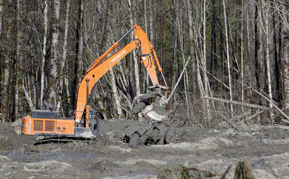 Photo - An excavator dislodges and stacks logs buried in deep mud at the scene of a deadly mudslide Wednesday, April 2, 2014, in Oso, Wash. Officials have so far confirmed the deaths of 29 people, although only 22 have been officially identified in information released Wednesday morning by the Snohomish County medical examiner's office. (AP Photo/Elaine Thompson)