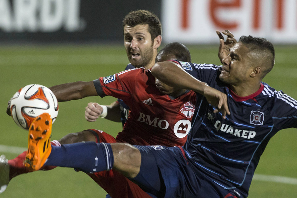 Photo - Chicago Fire's Quincy Amarikwa, right, and Gonzalo Segares, left, battle for the ball with Toronto FC 's Jackson Goncalves during the second half of a soccer game, Saturday, Aug. 23, 2014 in Toronto. (AP Photo/The Canadian Press, Chris Young)