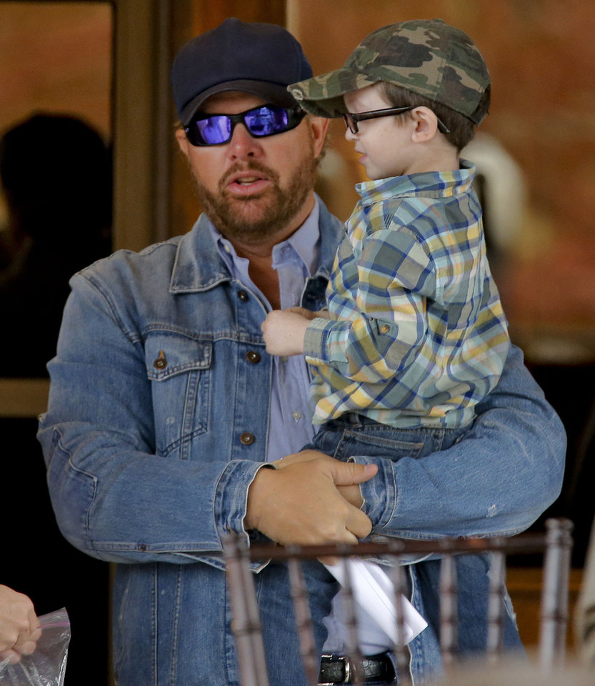 Photo - Toby Keith holds cancer patient Brock Hart, 5, as they hang out together before the grand opening of the Toby Keith Foundation's OK KIds Korral in Oklahoma City, Okla. on Thursday, Nov. 21, 2013. The Toby Keith Foundation was established to help children stricken with  cancer. The work has led to the construction of the OK Kids Korral as a home-away-from home in Oklahoma City for pediatric cancer patients. Photo by Chris Landsberger, The Oklahoman