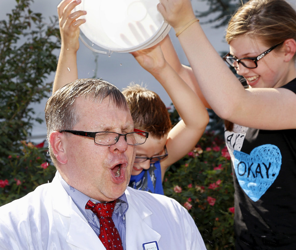 Photo - Dr. Brent Beson, medical director of the INTEGRIS MDA Neuromuscular Center, reacts after having ice water poured on him by his son, Nicholas, 9, and daughter, Caitlin, 13, when he and Bruce Lawrence, president and chief executive officer of INTEGRIS Health,  were willing participants Tuesday afternoon, Aug. 19, 2014,  after accepting the Ice Bucket Challenge in an effort to raise awareness of ALS services available  here in Oklahoma. The men had buckets of ice water poured on them in front of INTEGRIS Southwest Medical Center at SW 44 and Western Avenue. The Ice Bucket Challenge, sometimes referred to as the ALS Ice Bucket Challenge, is an activity involving dumping a bucket of ice water on a person's head to raise awareness and solicit donations for ALS treatment and research. It went viral throughout social media this summer. The challenge dares nominated participants to have a bucket of ice water poured on their head. One common stipulation gives 24 hours from the time they are nominated to complete the dare; otherwise, the participant is asked to donate money to charity. Photo by Jim Beckel, The Oklahoman