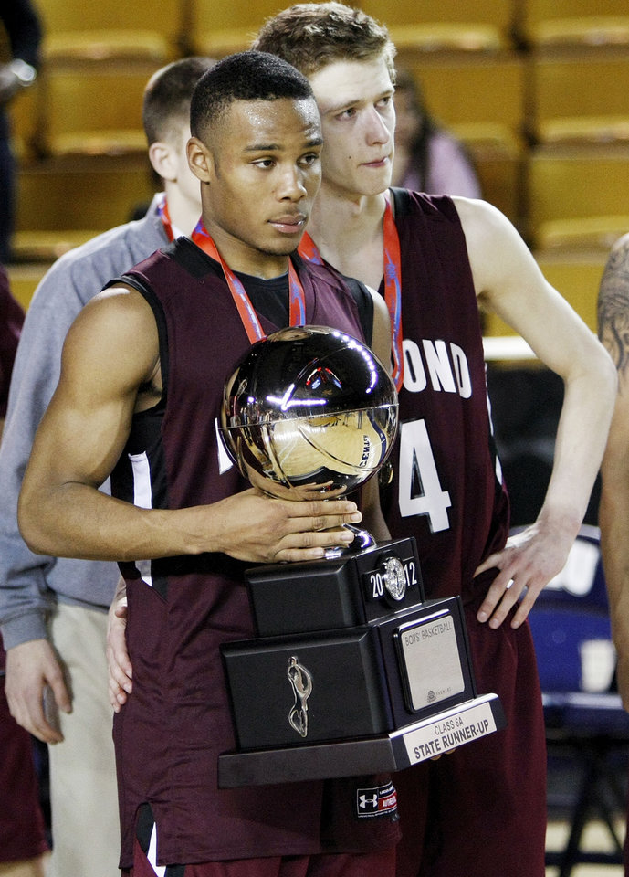 Edmond Memorial\'s Jordan Woodard (10) holds the runner-up trophy next to Jordan Thomas (4) after the Class 6A boys high school basketball state tournament championship game between Edmond Memorial and Tulsa Union at the Mabee Center in Tulsa, Okla., Saturday, March 10, 2012. Union won, 37-36. Photo by Nate Billings, The Oklahoman