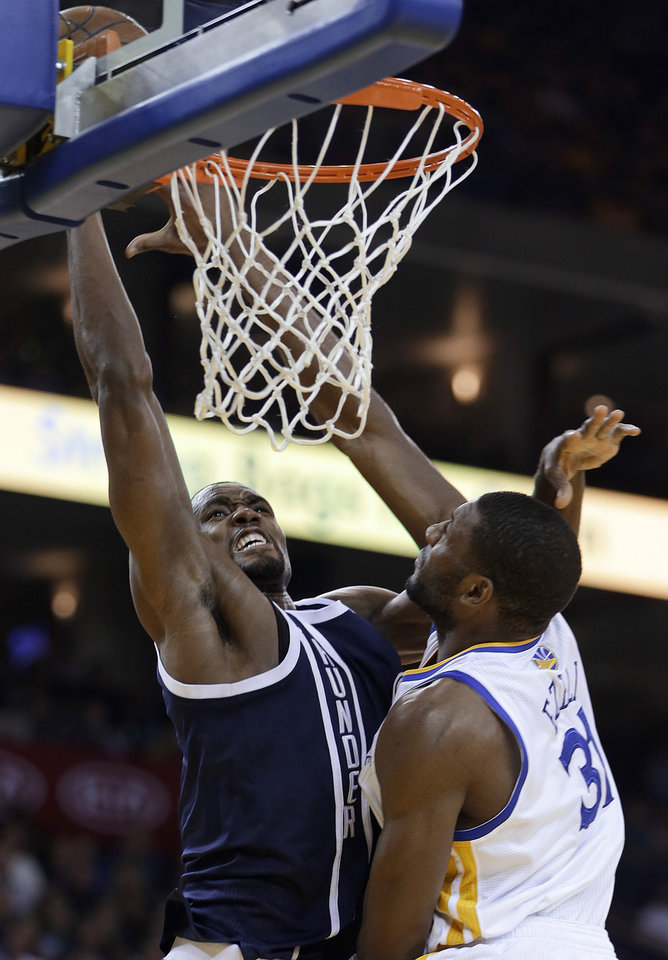 Oklahoma Thunder forward Serge Ibaka, left, lays up a shot against Golden State Warriors\' Festus Ezeli during the first half of an NBA basketball game Thursday, April 11, 2013, in Oakland, Calif. (AP Photo/Ben Margot) ORG XMIT: OAS103