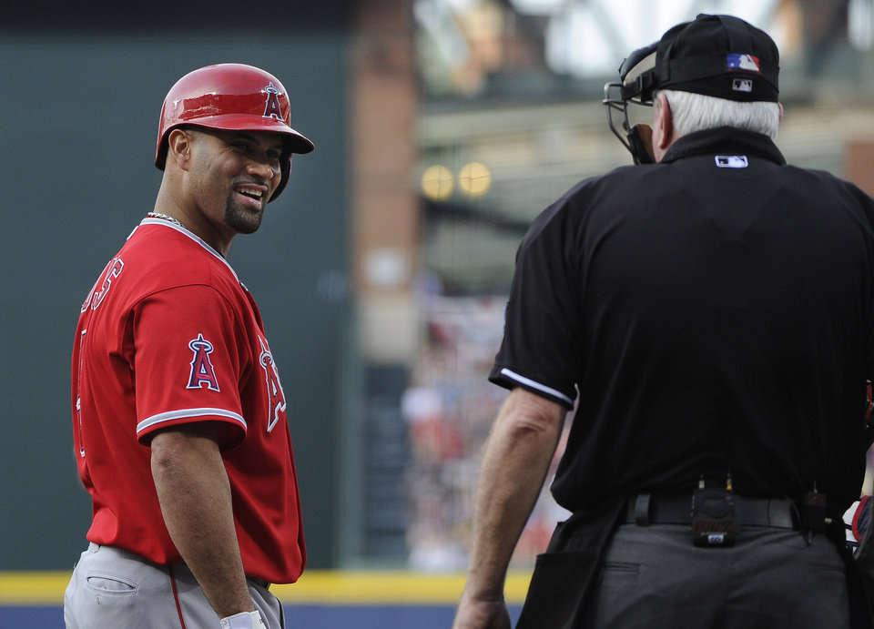 Photo - Los Angeles Angels' Albert Pujols, left, smiles at home plate umpire Brian Gorman during the first inning of a baseball game with the Atlanta Braves, Saturday, June 14, 2014, in Atlanta. (AP Photo/David Tulis)