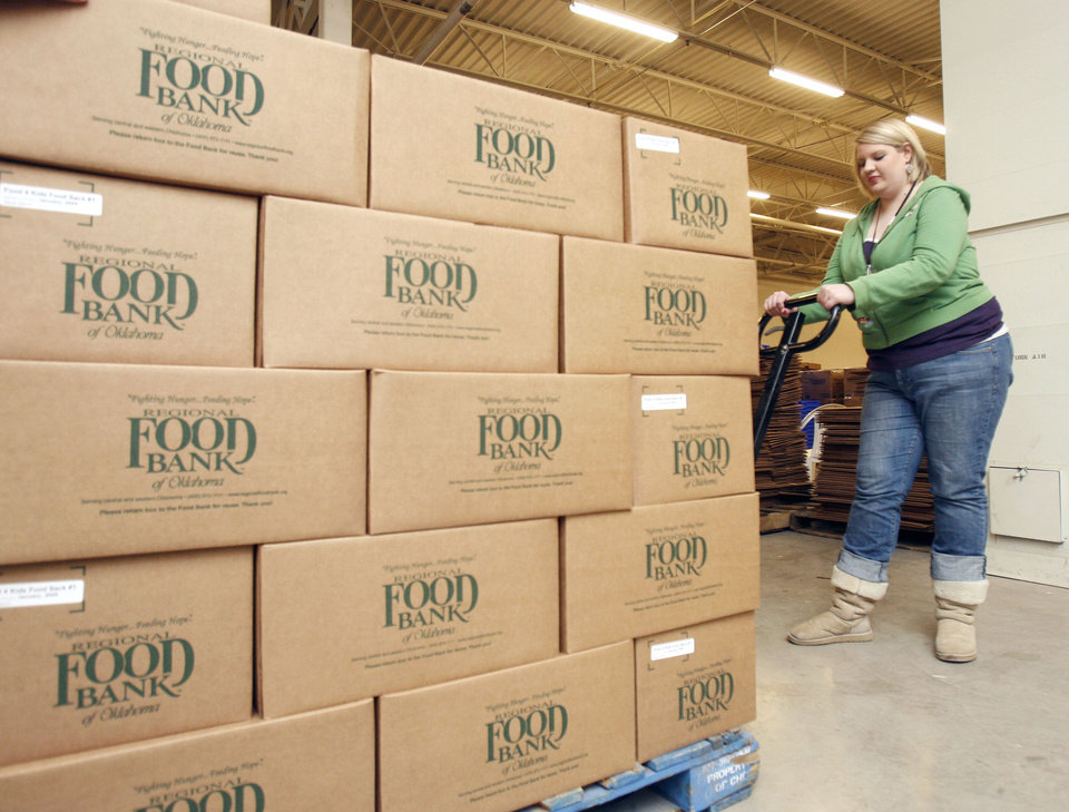 Photo - Americorps member Whittney David moves a large pallet of food as Putnam City Schools teachers pack backpacks with food at the Food Bank in Oklahoma City, OK, Saturday, Jan. 31, 2009. This is for the Food Bank's Food 4 Kids program that provides needy kids with backpacks full of food for them to eat during the weekend. BY PAUL HELLSTERN, THE OKLAHOMAN ORG XMIT: KOD