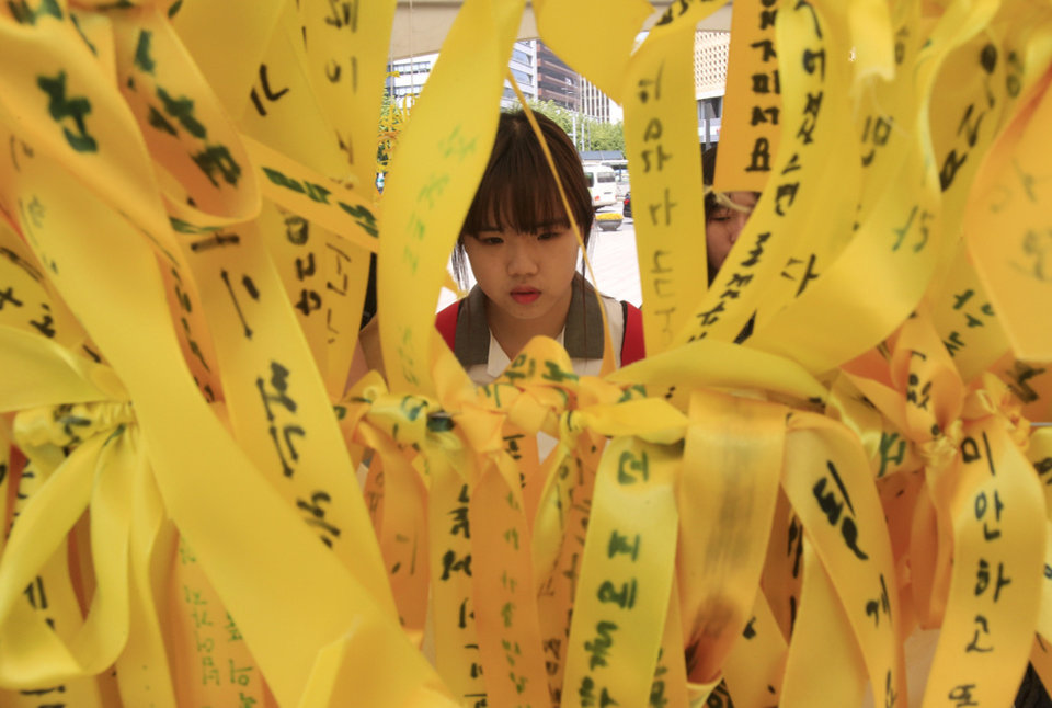 Photo - A high school student reads massages written on ribbons for the victims of the sunken ferry Sewol at a group memorial altar in Seoul, South Korea, Thursday, May 15, 2014. Prosecutors indicted the captain of the sunken South Korean ferry and three crew members on homicide charges Thursday, alleging they were negligent and failed to protect more than 300 people missing or dead in the disaster. Less serious indictments were issued against the 11 other crew members responsible for navigating the vessel.(AP Photo/Ahn Young-joon)