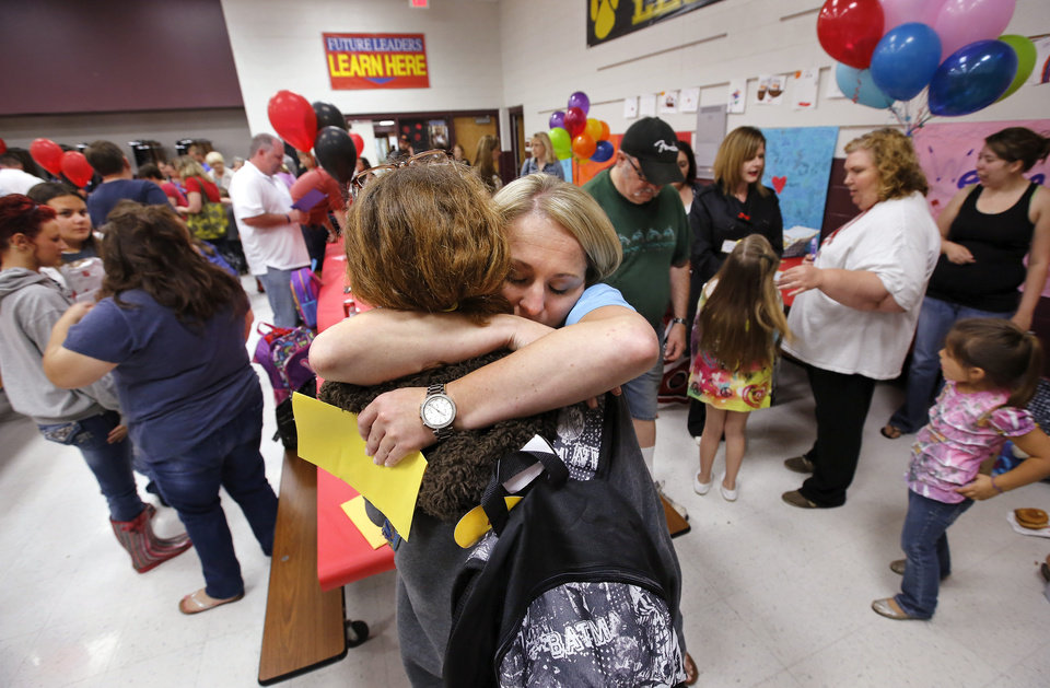 Photo - Kindergarten teacher Erin Baxter hugs a parent while others visit around them.  There was lots of hugging and plenty of joy at Eastlake Elementary School on SW 134, when Eastlake School hosted a reunion of students, parents, teachers and families from Plaza Towers Elementary School on Thursday, May 23, 2013. Seven students died at Plaza Towers School in Monday's EF-5 tornado, which also destroyed the school.  Photo  by Jim Beckel, The Oklahoman.