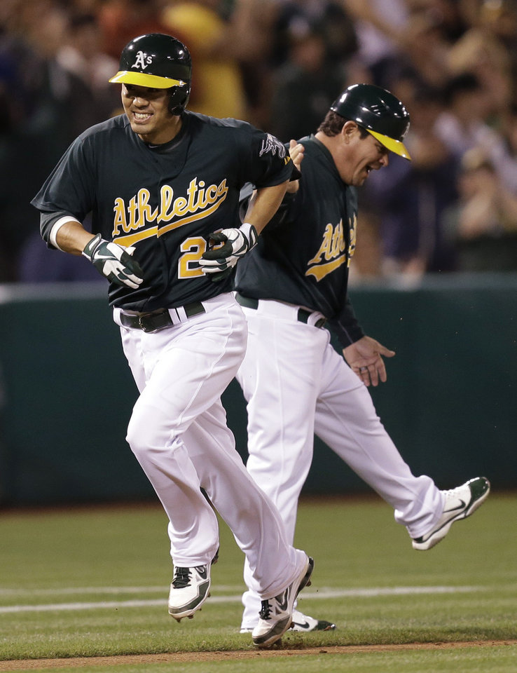 Photo - Oakland Athletics' Kurt Suzuki, left, runs the bases past third base coach Mike Gallego after Suzuki hit a three run home run off Tampa Bay Rays' David Price in the fifth inning of a baseball game Friday, Aug. 30, 2013, in Oakland, Calif. (AP Photo/Ben Margot)