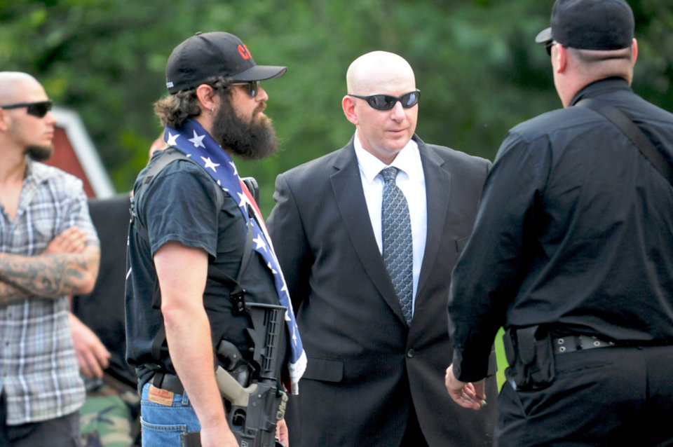 In this July 31, 2013 photo, Gilberton Police Chief Mark Kessler, center, talks with members of the Constitutional Security Force outside Borough Hall before the Gilberton Borough Council meeting in Gilberton, Pa. Kessler says he expects to be fired for posting incendiary videos in which he rants obscenely about the Second Amendment and liberals while spraying machine-gun fire with borough-owned weapons. (AP Photo/Republican-Herald, Jacqueline Dormer)