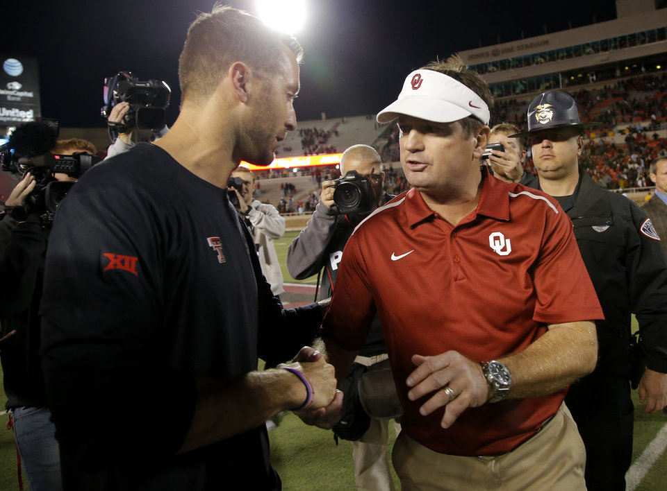 Photo - Oklahoma coach Bob Stoops meets with Texas Tech coach Kliff Kingsbury after a college football game between the University of Oklahoma Sooners (OU) and the Texas Tech Red Raiders at Jones AT&T Stadium in Lubbock, Texas, Saturday, November 15, 2014.  Photo by Bryan Terry, The Oklahoman