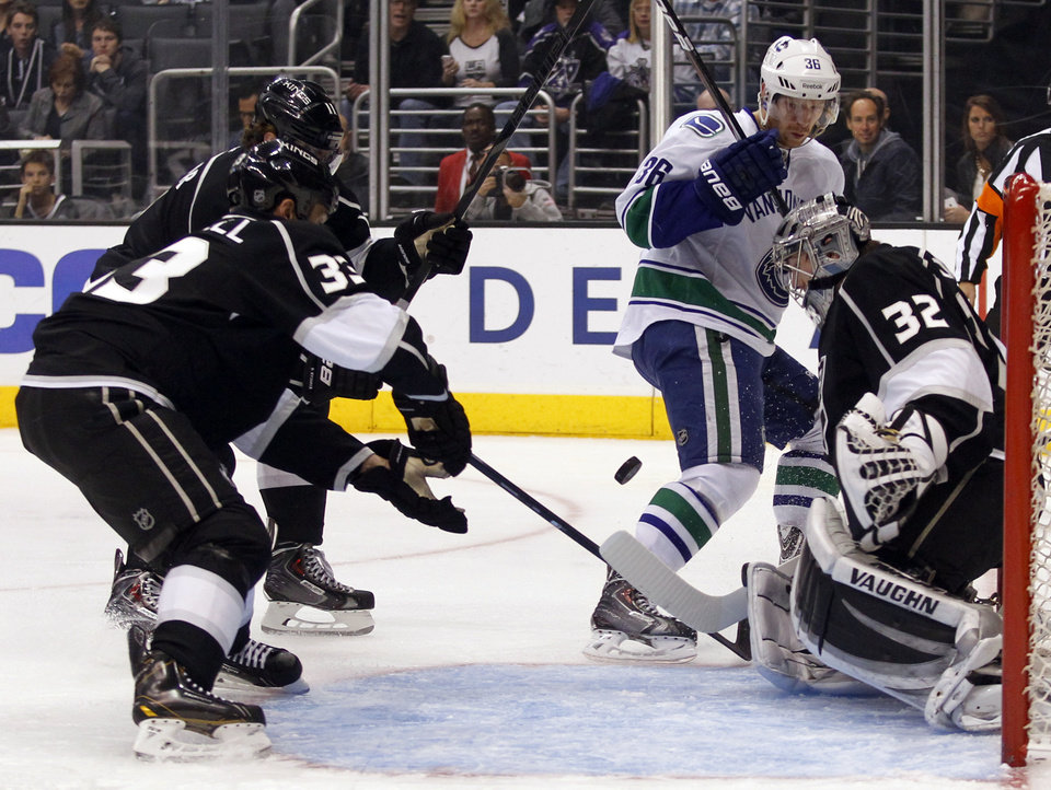 Photo - Los Angeles Kings goalie Jonathan Quick (32) stops a shot by Vancouver Canucks right wing Jannik Hansen (36), of Denmark ,with Kings center Anze Kopitar (11), of Slovenia, and defenseman Willie Mitchell (33) defending during the first period of an NHL hockey game on Saturday, Jan. 4, 2014, in Los Angeles. (AP Photo/Alex Gallardo)