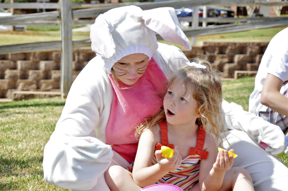 Photo -  The Easter Bunny, portrayed by Morgan Fitzgerald, pats the head of Brynn McDowell, 4, of Edmond, during an Easter open house at Touchmark at Coffee Creek. Photo by M. Tim Blake, For The Oklahoman   M. Tim Blake