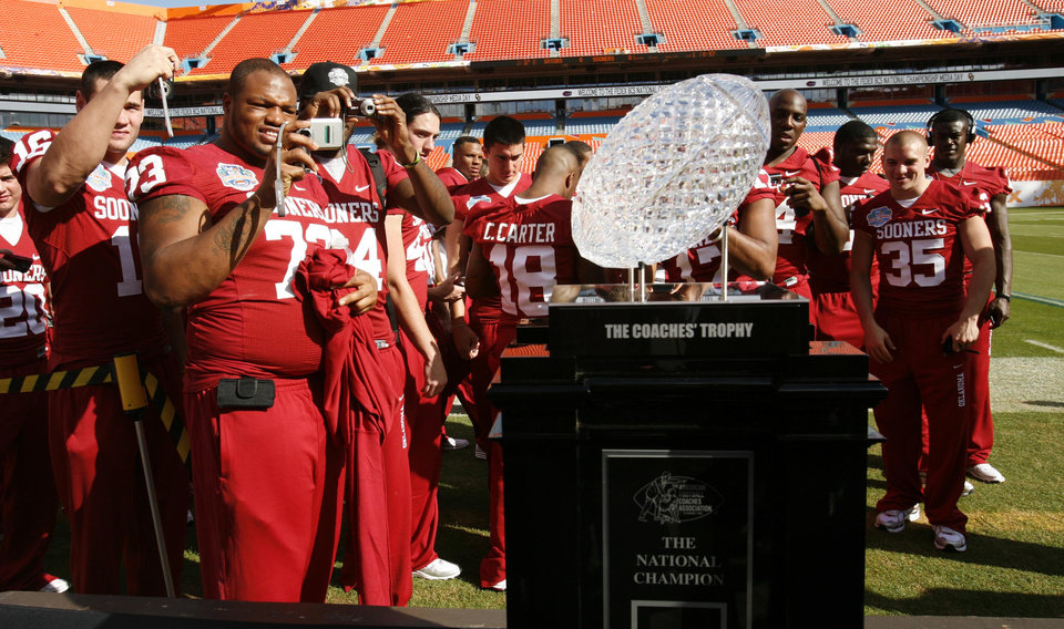 Photo - COLLEGE FOOTBALL / BCS NATIONAL CHAMPIONSHIP GAME / BOWL GAME / BOWL CHAMPIONSHIP SERIES: University of Oklahoma players admire the BCS Championship trophy during media day at Dolphin Stadium in Miami Monday Jan. 5, 2009. OU will play Florida for the BCS Championship Thursday Jan. 8, 2009.(AP Photo/Lynne Sladky) ORG XMIT: MH114