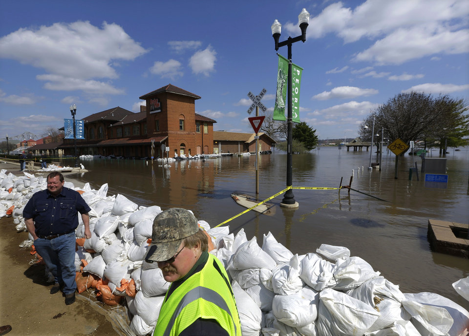 Peoria Maintenance Engineer Jim Clark, right bottom, monitors the sand bag wall holding back the Illinois River from recent flooding Wednesday, April 24, 2013, in Peoria, Ill. The Illinois River finally crested Tuesday at 29.35 feet, eclipsing a 70-year record in Peoria. (AP Photo/Seth Perlman)