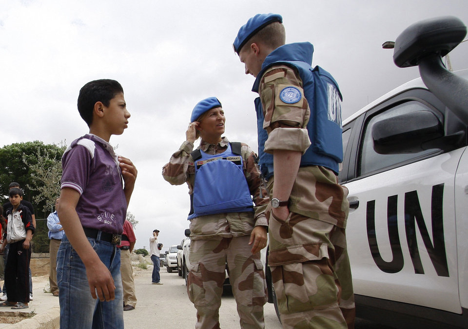 Photo -   In this picture taken during a UN observer-organized media tour, a Syrian boy talks with UN observers during their visit to Hama city, central Syria, on Thursday May 3, 2012. Syrian security forces stormed dorms at a northwestern university to break up anti-government protests there, killing at least four students and wounding several others with tear gas and live ammunition, activists and opposition groups said Thursday. (AP Photo/Muzaffar Salman)