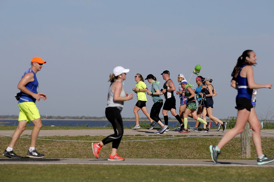 Photo - Runners pass by Lake Hefner during the Oklahoma City Memorial Marathon in Oklahoma City, Sunday, April 29, 2018. Photo by Bryan Terry, The Oklahoman