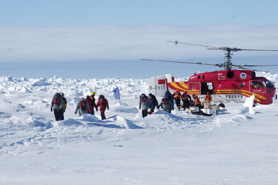 Photo - In this image provided by Australasian Antarctic Expedition, passengers trapped for more than a week on the icebound Russian research ship MV Akademik Shokalskiyin are rescued by a Chinese helicopter Thursday, Jan. 2, 2014.  The helicopter rescued all 52 passengers from the research ship that has been trapped in Antarctic ice, 1,500 nautical miles south of Hobart, Australia, since Christmas Eve after weather conditions finally cleared enough for the operation Thursday. (AP Photo/Australasian Antarctic Expedition, Jessica Fitzpatrick) EDITORIAL USE ONLY, ONE TIME USE, NO ARCHIVES; NO SALES