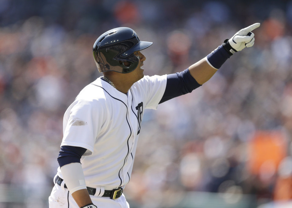 Detroit Tigers designated hitter Victor Martinez points to the crowd after his solo home run off Kansas City Royals starting pitcher James Shields during the second inning of a baseball game in Detroit, Monday, March 31, 2014. (AP Photo/Carlos Osorio)