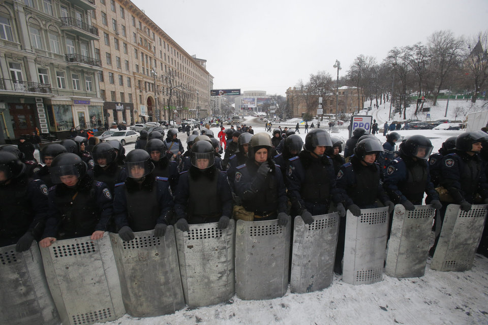 Photo - Ukrainian riot police block the road next to Pro-European Union activists gathered on the Independence Square in Kiev, Ukraine, Monday, Dec. 9, 2013. The policemen, wearing helmets and holding shields, formed a chain across Kiev's main street outside the city building. Organizers called on protesters to vacate the city hall and the other building which the opposition had used as its headquarters.  (AP Photo/Sergei Grits)
