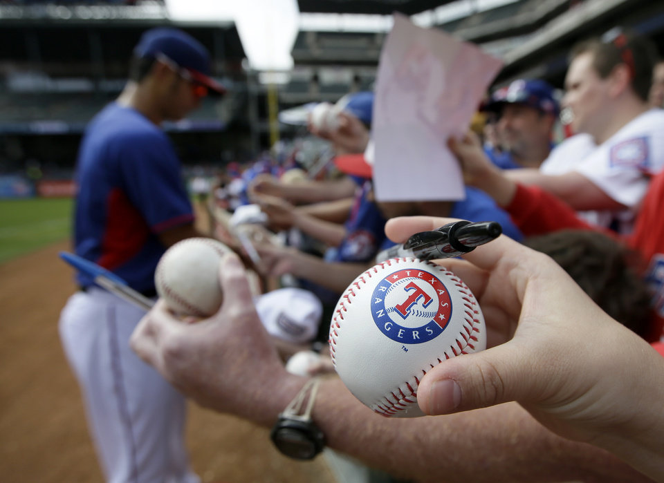 Photo - A fan holds a Texas Rangers stamped baseball waiting for a autograph from Yu Darvish of Japan before a baseball game against the Philadelphia Phillies, Monday, March 31, 2014, in Arlington, Texas. (AP Photo/Tony Gutierrez)