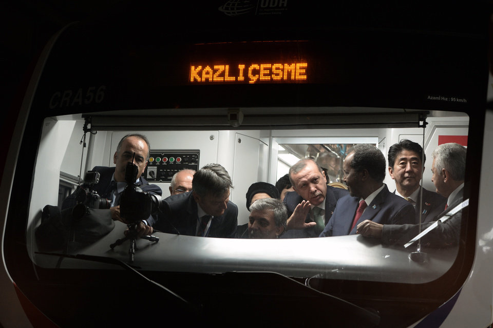 Photo - Japanese Prime Minister Shinzo Abe, second right, his Turkish counterpart Recep Tayyip Erdogan, fourth right, and other officials wait inside a train to cross the Bosporus after the inauguration of the tunnel called the  Marmaray in Istanbul, Turkey, Tuesday, Oct. 29, 2013. Turkey is for the first time connecting its European and Asian sides with a railway tunnel set to open Tuesday, completing a plan initially proposed by an Ottoman sultan about 150 years ago. The  Marmaray, is among a number of large infrastructure projects under the government of Prime Minister Recep Tayyip Erdogan that have helped boost the economy but also have provoked a backlash of public protest.(AP Photo)