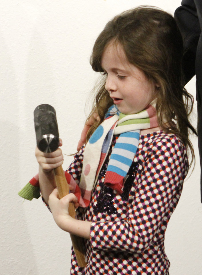 Photo - Lilly Ross, 7, holds a hammer during a wall breaking ceremony at the Oklahoma City National Memorial & Museum in Oklahoma City. Lilly is the daughter of Bob Ross, president and CEO of the Inasmuch Foundation.   Steve Gooch - The Oklahoman